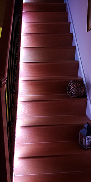 Wooden staircase illuminated by LED strips RGB Warm white